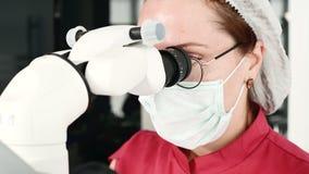 Donna del primo piano A in vetri con un dentista professionista che lavora con un microscopio stamotological professionale in lei video d archivio