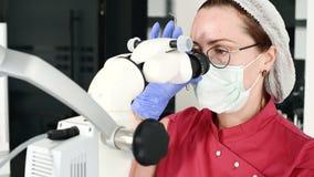 Donna del primo piano A in vetri con un dentista professionista che lavora con un microscopio stamotological professionale in lei stock footage