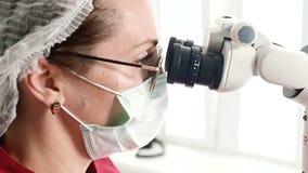Donna del primo piano A in vetri con un dentista professionista che lavora con un microscopio stamotological professionale in lei archivi video