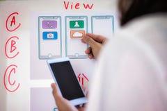 Donna del progettista di web che fa domanda del disegno di schizzo della prova di telefono cellulare in ufficio Concetto di proge immagini stock