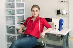 Donna del progettista del sarto nell'atelier dello studio che posa con nastro adesivo di misurazione e la macchina per cucire immagini stock