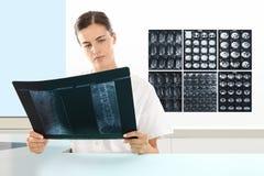 Donna del radiologo che controlla raggi x, sanità fotografie stock