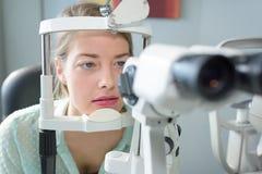 Donna del ritratto con la testa in attrezzatura dell'esame degli ottici fotografia stock
