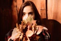 Donna del ritratto di autunno di modo con le foglie di acero gialle su fondo di legno giallo Bella donna di modo in autunno fotografie stock libere da diritti