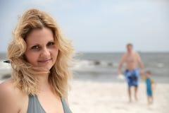 Donna del ritratto sopra sulla spiaggia e sulla famiglia di t dietro lei Immagini Stock Libere da Diritti