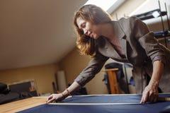 Donna del sarto da donna che lavora con nastro adesivo di misurazione in atelier immagini stock