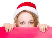 Donna del segno di Natale che dà una occhiata sopra il bordo rosso Fotografia Stock