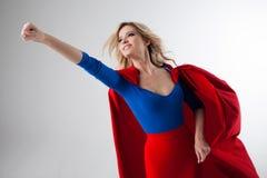 Donna del supereroe Giovane e bella bionda nell'immagine del superheroine nella crescita rossa del capo Immagini Stock Libere da Diritti
