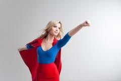 Donna del supereroe Giovane e bella bionda nell'immagine del superheroine nella crescita rossa del capo Immagini Stock