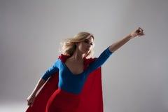 Donna del supereroe Giovane e bella bionda nell'immagine del superheroine nella crescita rossa del capo Fotografia Stock Libera da Diritti