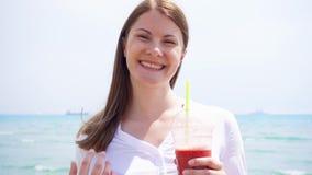 Donna del vegano con il frullato della fragola contro il mare al rallentatore La femmina adatta gode dello stile di vita sano archivi video