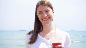 Donna del vegano con il frullato della fragola contro il mare al rallentatore La femmina adatta gode dello stile di vita sano video d archivio