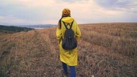 Donna del viaggiatore che cammina nel campo Ragazza che porta impermeabile giallo con lo zaino archivi video