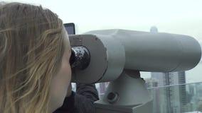 Donna del viaggiatore che guarda panorama della città dal binocolo turistico su Victoria Peak Hong Kong China Sguardo turistico d stock footage