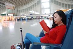 Donna del viaggiatore del passeggero in stazione ferroviaria e libro colto fotografie stock libere da diritti