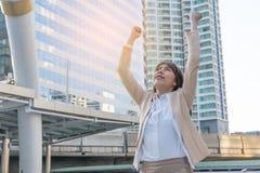 Donna del vincitore che celebra successo sul fondo della città Fotografia Stock