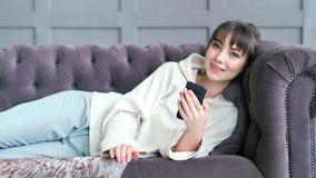 Donna dell'adolescente che si trova sullo strato nel messaggio di chiacchierata di scrittura del salone facendo uso dello smartph archivi video