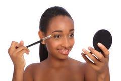 Donna dell'afroamericano che usando la spazzola dell'ombra di occhio Immagine Stock Libera da Diritti