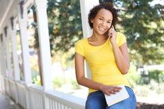 Donna dell'afroamericano sul portico sul telefono fotografie stock