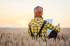 Donna dell'agricoltore che calcola il rendimento del raccolto dopo un giorno lungo fotografia stock