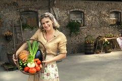 Donna dell'agricoltore che mostra i prodotti della terra presi appena  Fotografie Stock