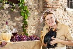 Donna dell'agricoltore che mostra il suo gallo nero Fotografia Stock