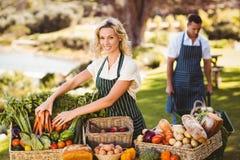 Donna dell'agricoltore che riordina una tavola di alimento locale Fotografie Stock