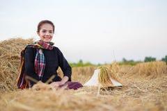 Donna dell'agricoltore che riposa con la paglia nel campo Fotografie Stock