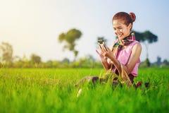 Donna dell'agricoltore che utilizza uno Smart Phone in un giacimento del riso Fotografie Stock