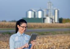 Donna dell'agricoltore con la compressa ed il silos Fotografie Stock Libere da Diritti