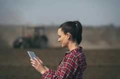 Donna dell'agricoltore con la compressa ed il trattore nel campo Fotografia Stock