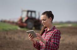 Donna dell'agricoltore con la compressa ed il trattore nel campo Immagine Stock
