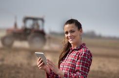 Donna dell'agricoltore con la compressa ed il trattore nel campo Immagine Stock Libera da Diritti