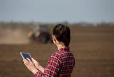 Donna dell'agricoltore con la compressa ed il trattore nel campo Fotografia Stock Libera da Diritti