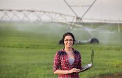 Donna dell'agricoltore davanti al sistema di innaffiatura fotografia stock