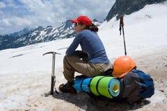 Donna dell'alpinista che si siede sul suo zaino Immagini Stock