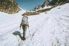 Donna dell'alpinista con lo zaino che scala alla cima della montagna Immagine Stock