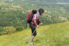 Donna dell'alpinista con lo zaino su un prato con i fiori Fotografie Stock Libere da Diritti