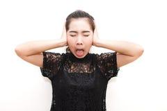 Donna dell'Asia che infastidisce e che copre le orecchie di sue mani guardi il simile Fotografia Stock Libera da Diritti