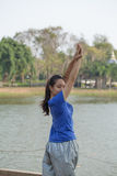 Donna dell'Asia che si scalda prima del suo allenamento di mattina nel giardino Immagine Stock Libera da Diritti
