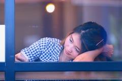 Donna dell'Asia che si siede alla tavola della barra e che manda un sms al suo cellulare Fotografie Stock Libere da Diritti