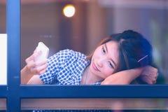 Donna dell'Asia che si siede alla tavola della barra e che manda un sms al suo cellulare Immagini Stock Libere da Diritti