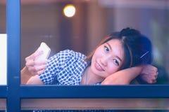 Donna dell'Asia che si siede alla tavola della barra e che manda un sms al suo cellulare Immagini Stock