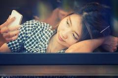 Donna dell'Asia che si siede alla tavola della barra e che manda un sms al suo cellulare Fotografia Stock Libera da Diritti