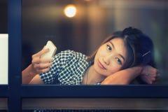 Donna dell'Asia che si siede alla tavola della barra e che manda un sms al suo cellulare Fotografie Stock