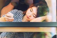 Donna dell'Asia che si siede alla tavola della barra e che manda un sms al suo cellulare Fotografia Stock