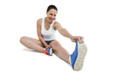 Donna dell'atleta che allunga il suo tendine del ginocchio Immagini Stock