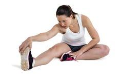 Donna dell'atleta che allunga il suo tendine del ginocchio Fotografia Stock