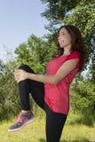 Donna dell'atleta che allunga le sue gambe dopo gli sport all'aperto Fotografia Stock Libera da Diritti