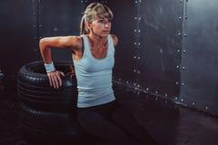 Donna dell'atleta che fa spinta-UPS su addestramento del banco Fotografia Stock